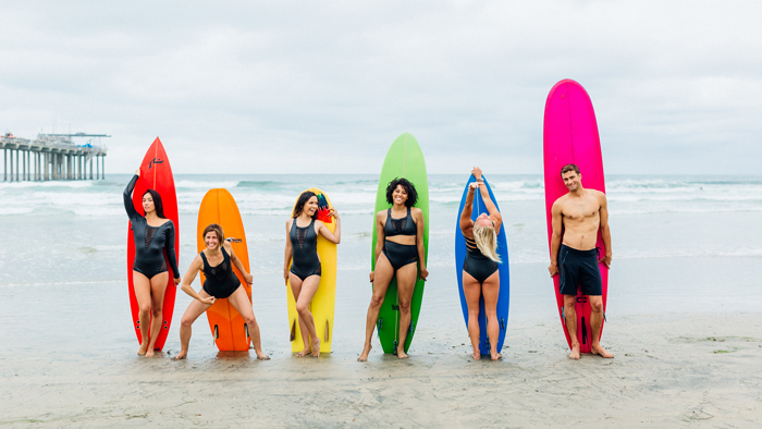 Surfer girls standing by surf boards on the beach